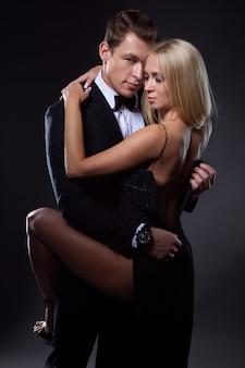 Un hombre en un arrebato de pasión desabotona el vestido de su amada joven, quien lo abraza gentilmente