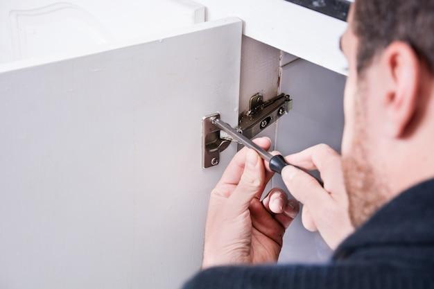 Hombre arreglando un armario con un destornillador
