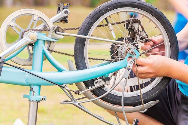 El hombre está arreglando la bicicleta, enfocado selectivamente.