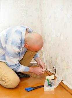 Hombre arreglando una toma de corriente dentro de las puertas