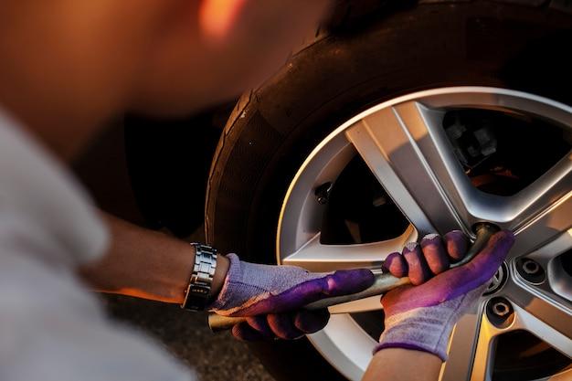 Hombre arreglando los tornillos de la rueda