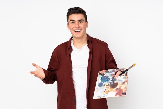 Hombre artista adolescente sosteniendo una paleta aislada en blanco