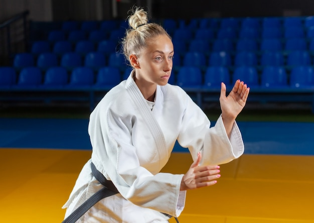 Hombre artista marcial en kimono blanco con cinturón negro se encuentra en posición de lucha interior. retrato deportivo
