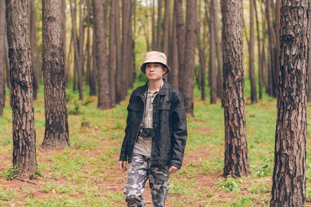 El hombre de asia usa camisa y chaqueta vaquera, sombrero y pantalones de camuflaje están caminando y tomando fotos en el bosque