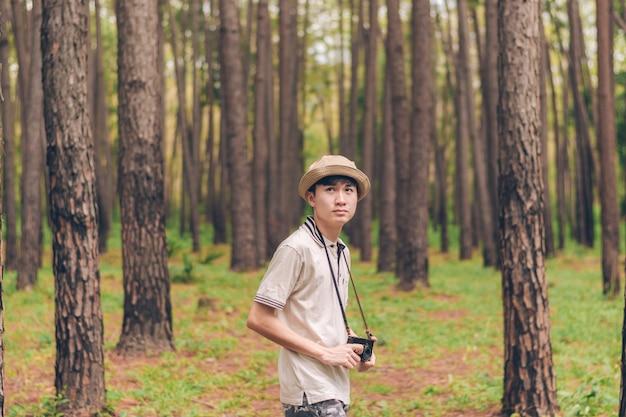 El hombre de asia usa camisa, sombrero y pantalones de camuflaje, camina y toma fotos en el bosque