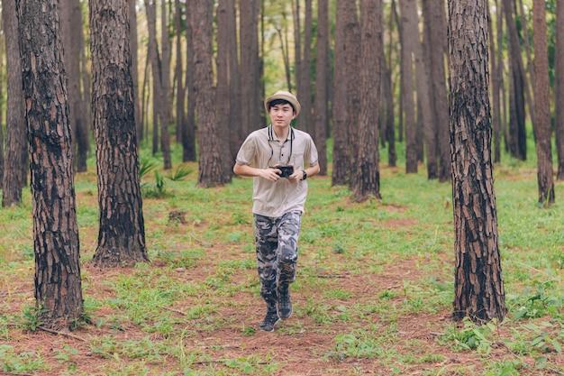 El hombre de asia usa camisa, sombrero y pantalones de camuflaje, corre y toma fotos en el bosque