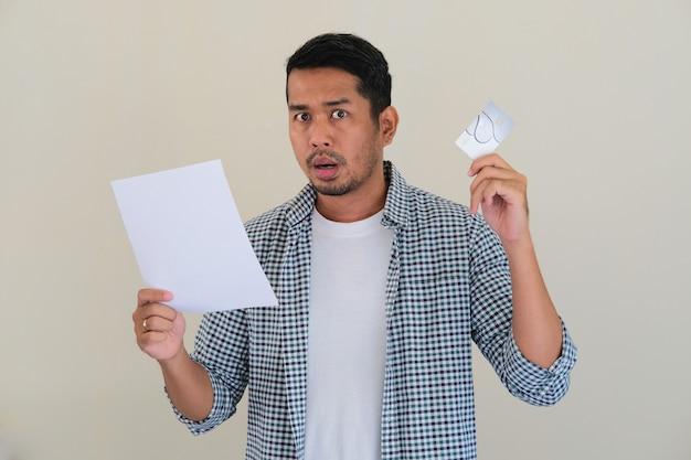 Hombre asiático adulto que muestra la expresión de la cara de sorpresa después de leer su carta de facturación de la tarjeta de crédito