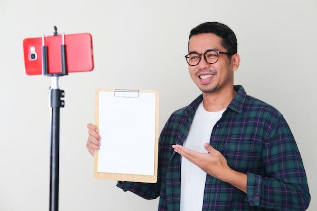 Hombre asiático adulto sonriendo mientras presenta papel blanco vacío durante la conferencia telefónica móvil