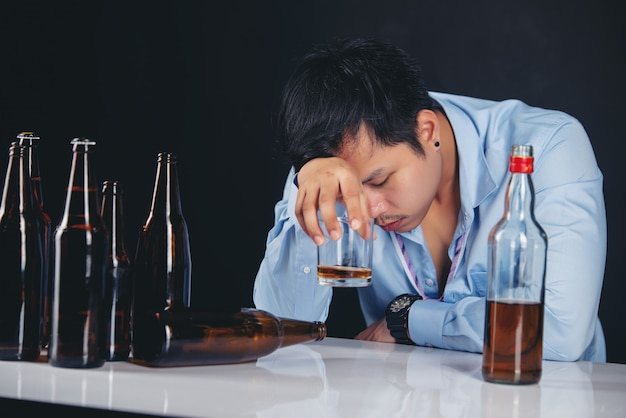 Hombre asiático alcohólico bebiendo whisky con muchas botellas