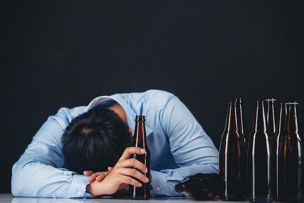 Hombre asiático alcohólico con muchas botellas de cerveza
