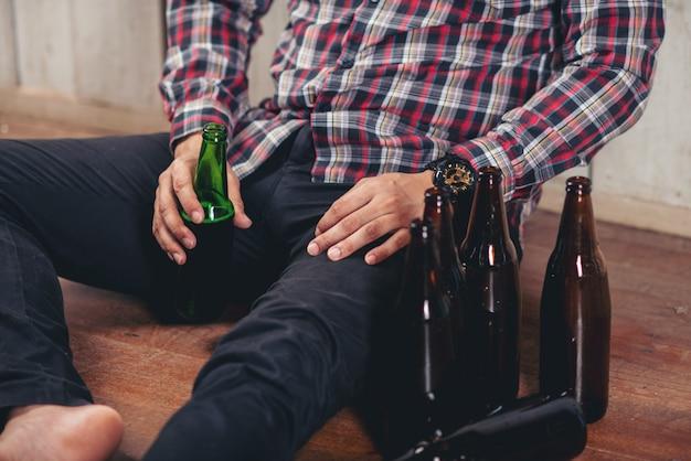 Hombre asiático alcohólico sentado solo con botellas de cerveza