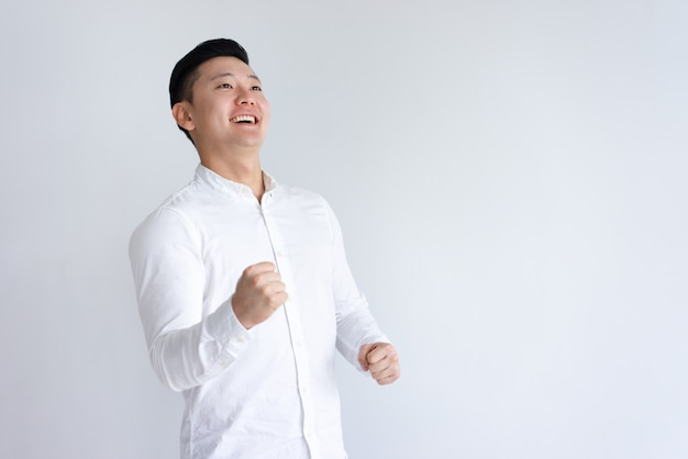 Hombre asiático alegre que bombea los puños y que mira lejos