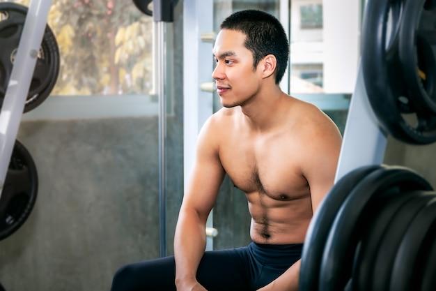 Hombre asiático atlético en forma y saludable sonriendo en el gimnasio después del entrenamiento.