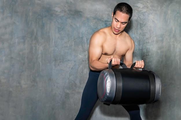 Hombre asiático atlético perfecto entrenamiento con bolsa de poder en el gimnasio.