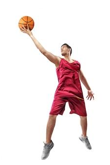 Hombre asiático atractivo del jugador de básquet en uniforme rojo que salta con la bola en manos