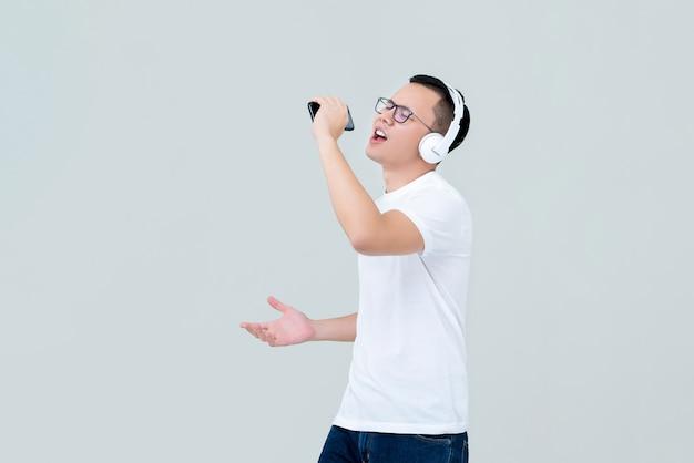Hombre asiático con auriculares escuchando música y cantando