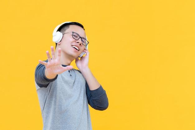 Hombre asiático con auriculares escuchando música y haciendo gesto de parada