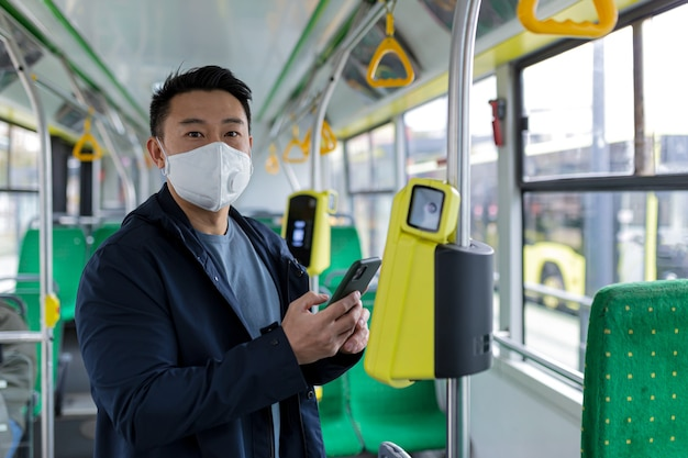 Hombre asiático en autobús de transporte público con máscara médica protectora compra billete electrónico por teléfono, pasajero en autobús vacío
