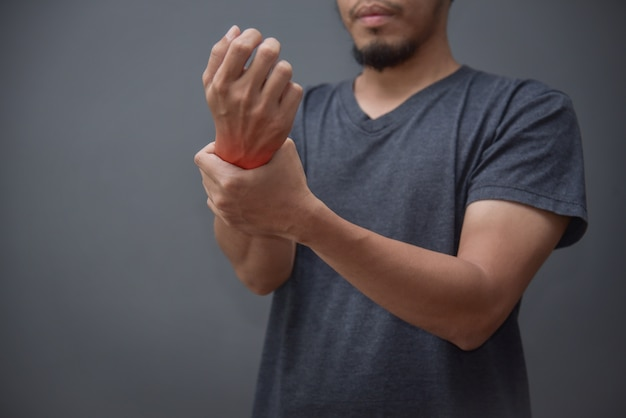 Hombre asiático de la barba que tiene dolor de muñeca