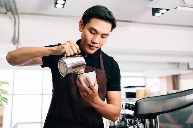 Hombre asiático barista en un delantal, vertió intencionalmente leche caliente en un café negro espresso caliente.
