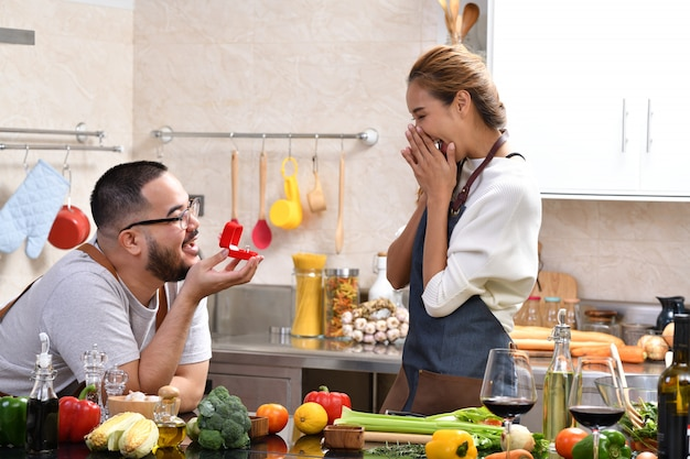 Hombre asiático con caja roja con anillo haciendo proponer a su novia en la cocina