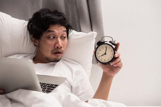 El hombre asiático en la cama mira el despertador cuando se despierta después de dormir mientras trabajaba en la computadora