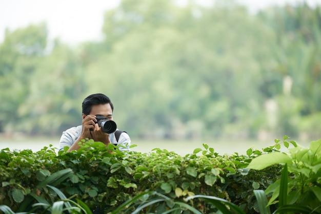 Hombre asiático con cámara profesional mirando por encima del seto verde en el parque y tomando fotos