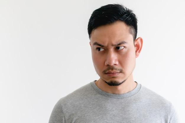 Hombre asiático en camiseta gris está mirando el espacio vacío