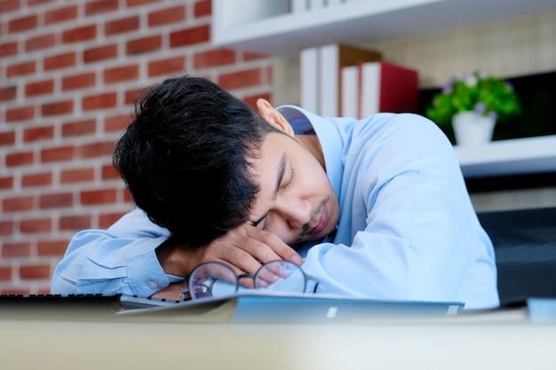 Hombre asiático cansado que duerme en el escritorio de oficina. joven empresario con anteojos con exceso de trabajo y se quedó dormido