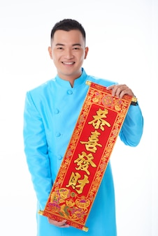 Hombre asiático en chaqueta tradicional posando con desplazamiento de kanji ornamentales