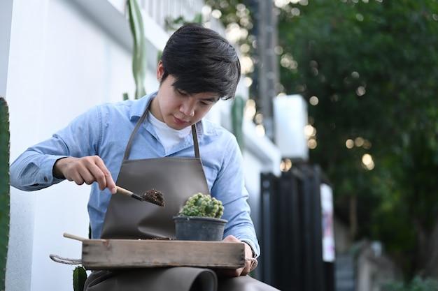 Hombre asiático coleccionista de cactus está plantando cactus en la maceta en el jardín de su casa.