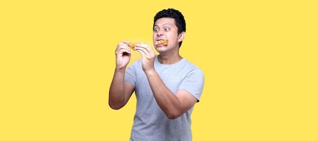 Hombre asiático está comiendo pollo frito deliciosamente sobre fondo amarillo