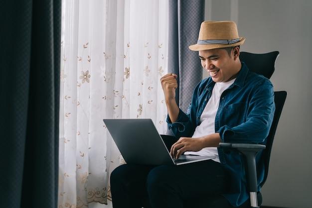 Hombre asiático comprueba su éxito de ventas en línea en casa, concepto de trabajo desde casa