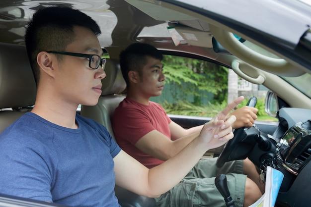 Hombre asiático conduciendo coche y amigo con mapa apuntando hacia adelante