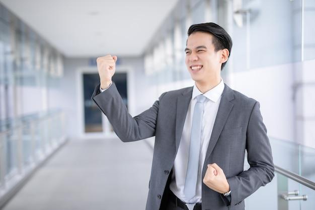 Hombre asiático confidente que sostiene la mano en la barbilla y que sonríe mientras está de pie en su lugar de trabajo en la oficina