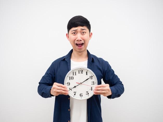 Hombre asiático conmocionado cara hodling reloj a las diez y ocho de la mañana en su mano concepto tardío en blanco