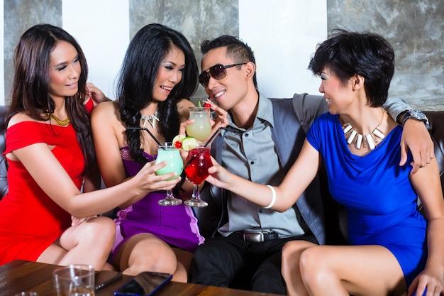 Hombre asiático coqueteando con mujeres en discoteca