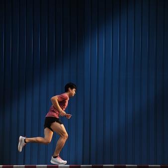 Hombre asiático corriendo en la acera correr, concepto de ciudad ejecutar