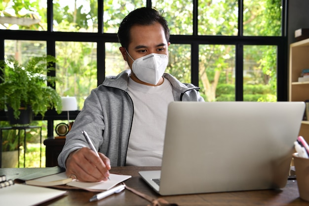 Hombre asiático en cuarentena y distanciamiento social con máscara quirúrgica mientras trabajaba desde su hogar durante la pandemia de coronavirus covid-19