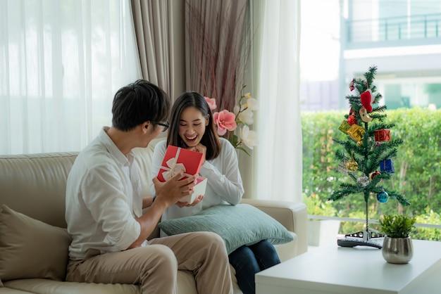 El hombre asiático le da a la mujer una caja de regalo roja en la que hay una botella de perfume.