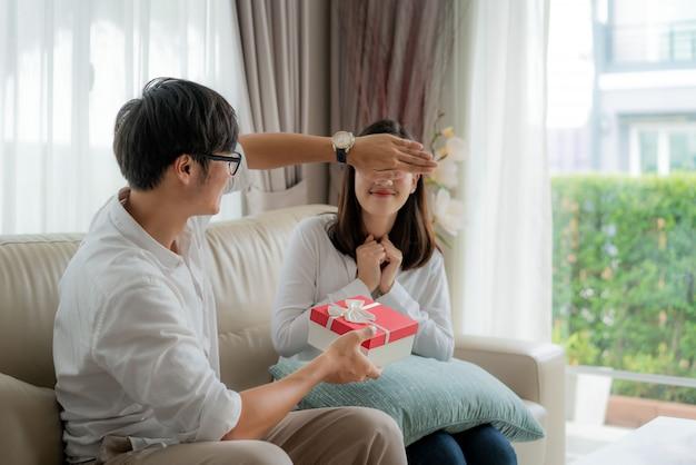 El hombre asiático le da a la mujer una caja de regalo roja.