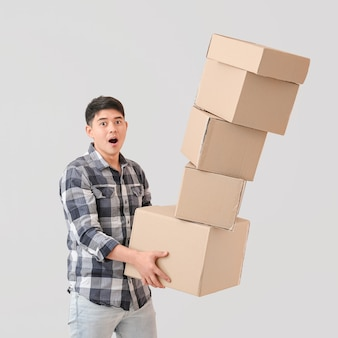 Hombre asiático dejando caer cajas de mudanza en luz