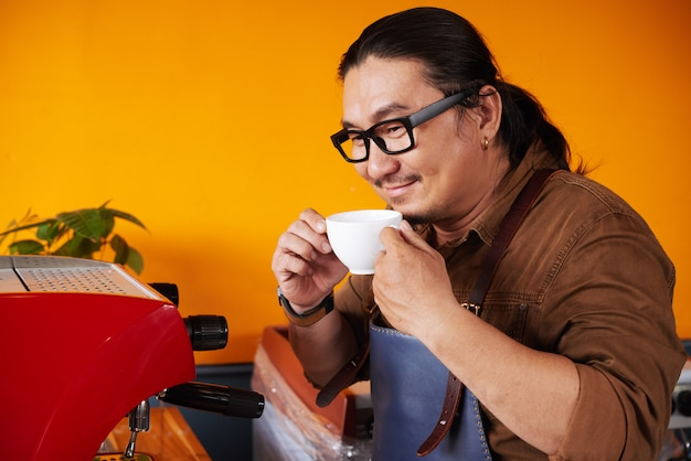 Hombre asiático en delantal de pie junto a la máquina de café espresso, sosteniendo la taza y oliendo café