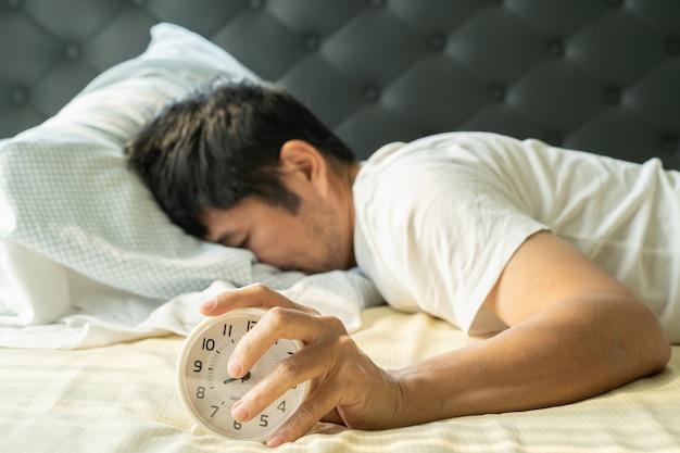 El hombre asiático se despierta por la mañana y la mano alcanza el despertador