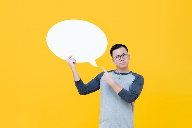Hombre asiático dudoso que señala en el bocadillo de diálogo vacío