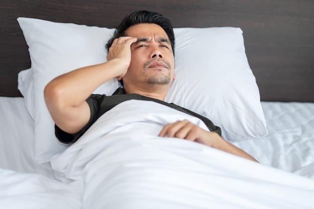 Un hombre asiático duerme con dolor de cabeza sujetándose la cabeza con ansiedad en la cama blanca del dormitorio.