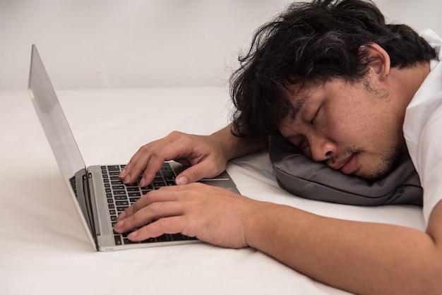 El hombre asiático está durmiendo en la cama en el dormitorio deja su trabajo en la computadora.