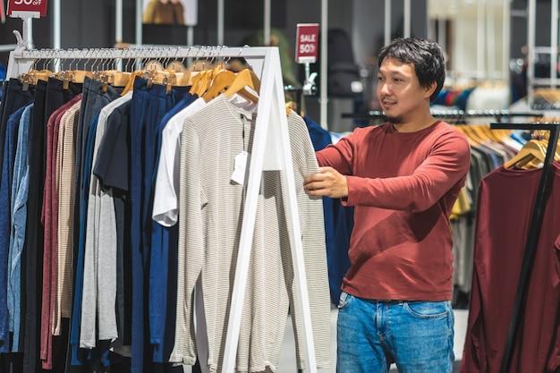 Hombre asiático elegante con la barba que elige la ropa en tienda de ropa en el centro comercial