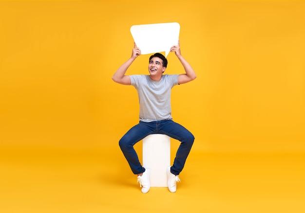 Hombre asiático emocionado sentado y sosteniendo burbujas de discurso en blanco. mirando hacia arriba con una sonrisa en la pared amarilla.
