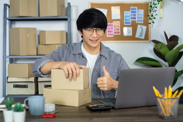 Hombre asiático emprendedor inicio emprendedor de pequeñas empresas pyme hombre independiente que trabaja con caja para empaquetado de marketing en línea y escena de entrega en la oficina en casa, concepto de vendedor de negocios en línea.